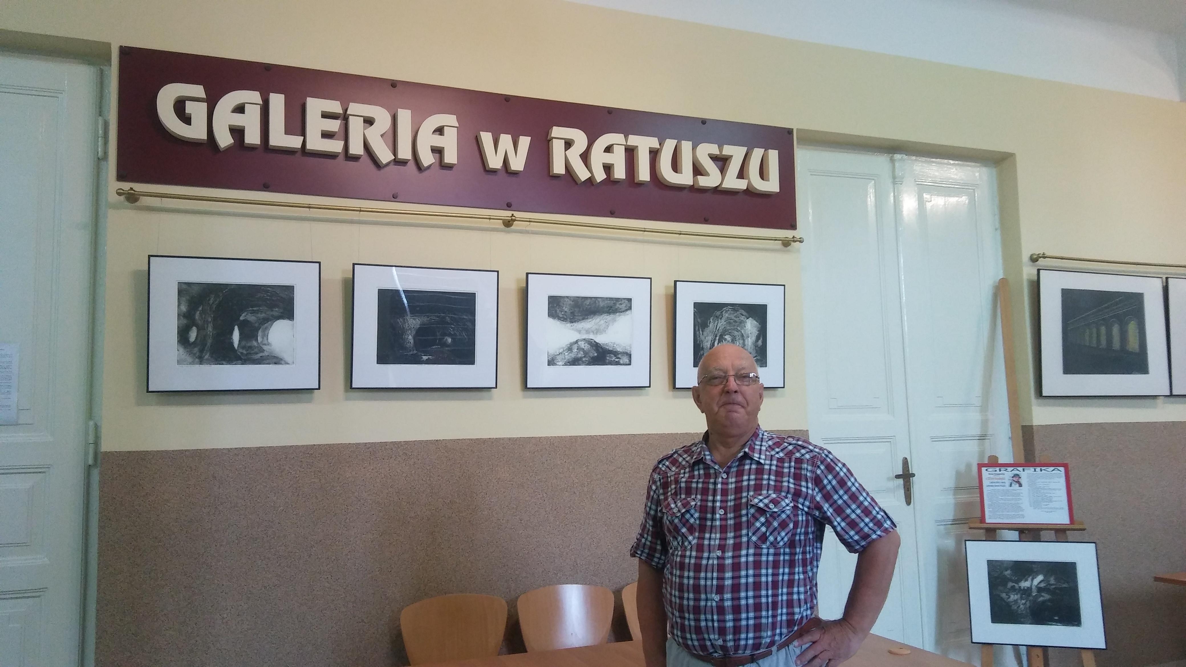 Zdjęcie artysty Matuszewskiego na tle wystawy