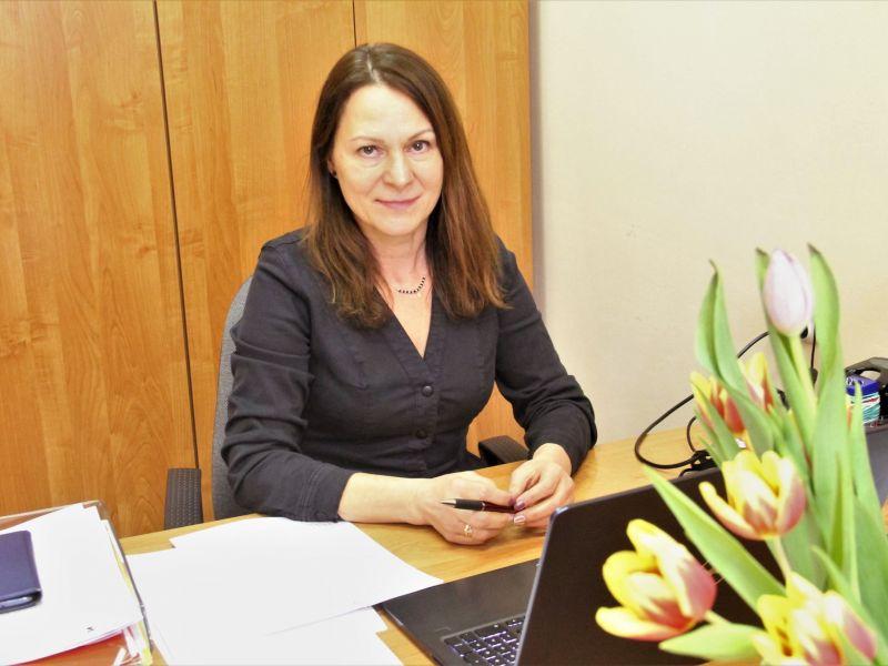 Na zdjęciu p. Wanda Rybak - pełnomocnik prezydenta ds. seniorów,  siedzi przy biurku, na biurku laptop i bukiet kwiatów