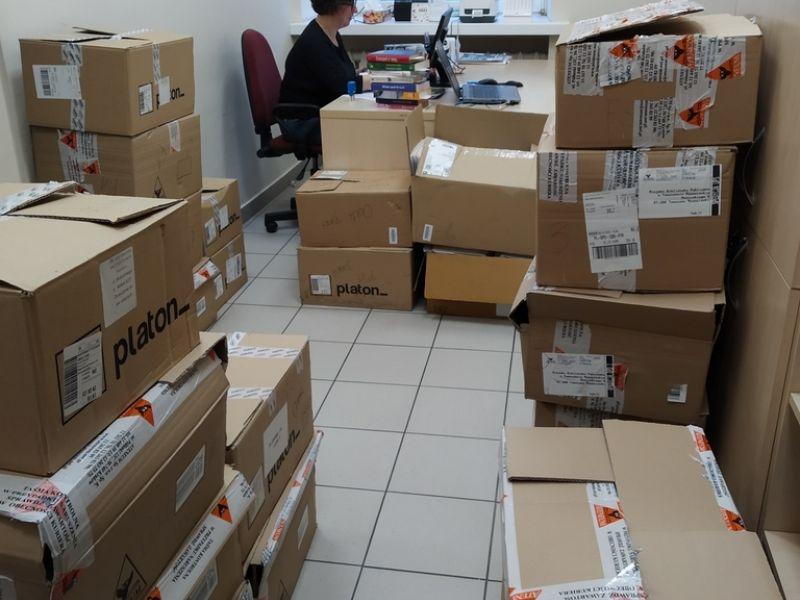 Na zdjęciu pomieszczenie biurowe w MBP zastawione pudełkami wypełnionymi książkami. W tle pracownik biblioteki przy biurku