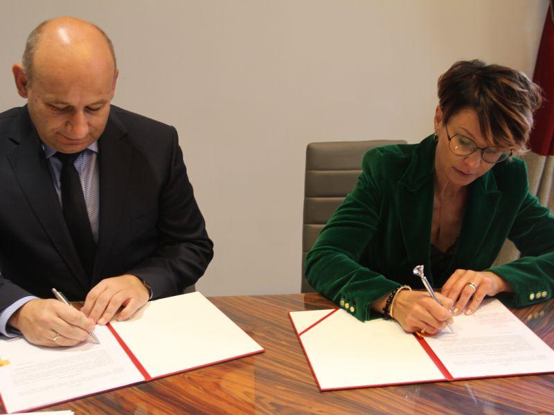 kobieta i mężczyzna siedzą przy stole i podpisują dokumenty