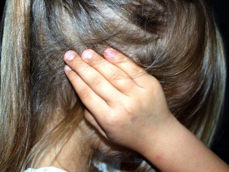 Dziewczynka stou bokiem i zakrywa uszy