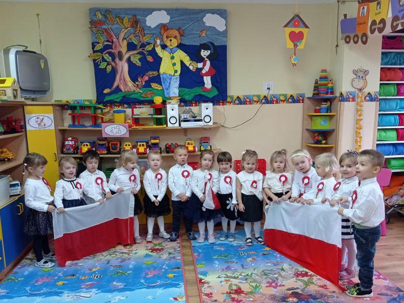 Na zdjęciu porzedszkolaki w biało-czerwonych strojach prezentują flagi biało-czerwone w ramach Narodowego Święta Niepodległości