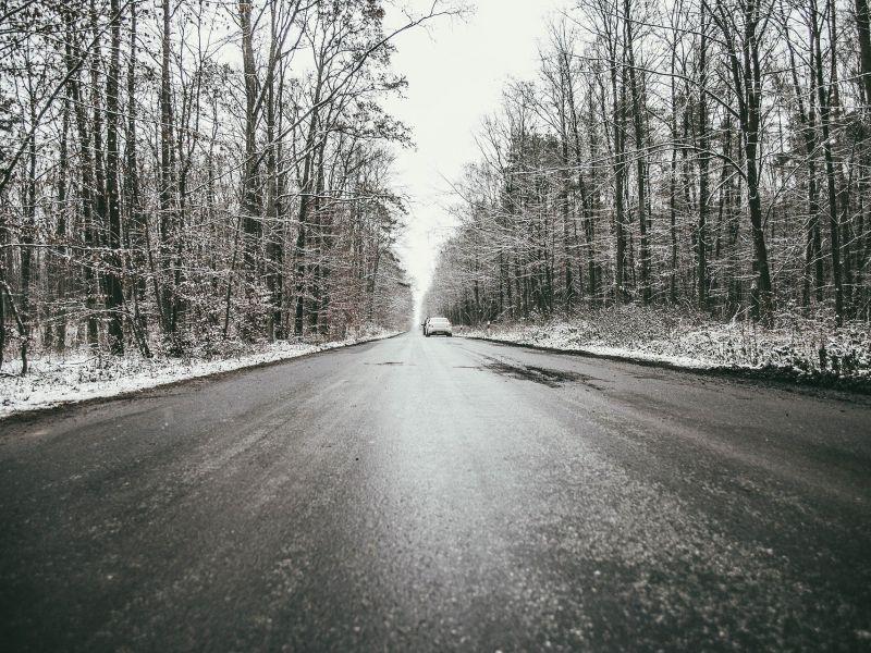 Na zdjęciu droga przez las, na powierzchni drogi gołoledź, wokół las i zamarznięty śnieg