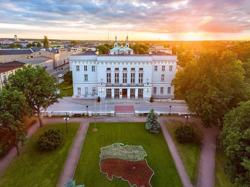 na zdjęciu gmach urzędu Miasta w Tomaszowie Mazowieckim, sfotografowany z drona, przed urzedem trawnik z widoczną kompozycją z kwiatów w kształcie konturu Polski