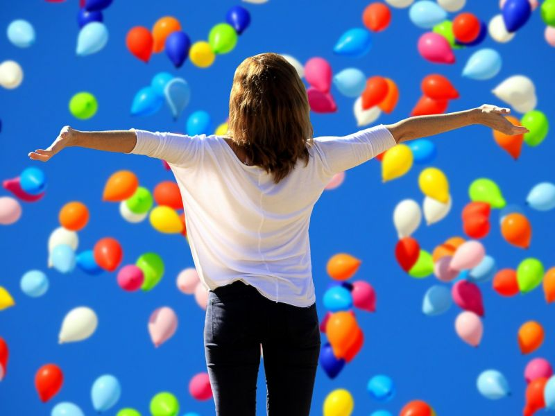 Na zdjęciu kobieta z rozpostartymi rękoma, stojąca tyłem przed ścianą wznoszących się w powietrze kolorowych balonów