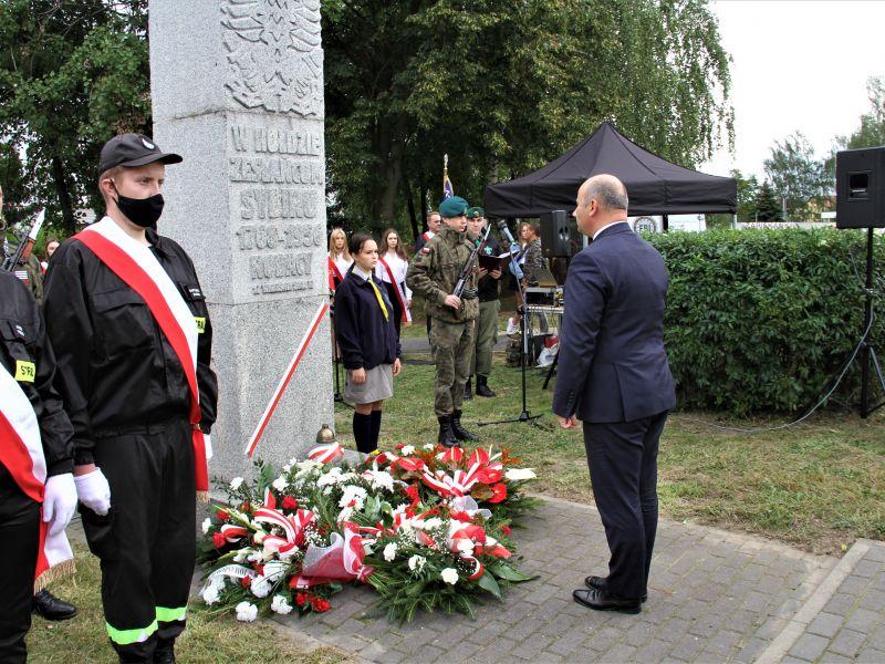 Na zdjęciu widać pomnik Sybiraków. Pod nim leżą kwiaty. Prezydent stoi przed nim składając hołd, obok stoją poczty sztandarowe.