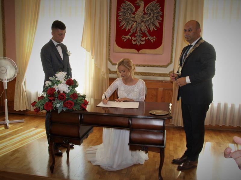 kobieta w białej sukni siedzi przy stole podpisuje dokument wokół niej stoi dwóch mężczyzn