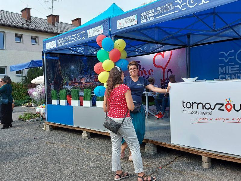 Na zdjęciu stoisko promocyjne miasta i MCK na dozynkach w Rogowie. Przed stoiskami dwie panie ropzmawiają