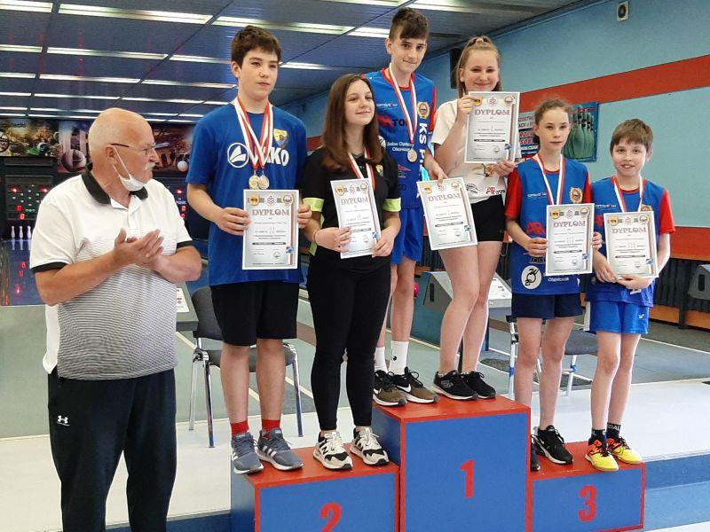 Na zdjęciu młodzicy w kręglarstwie na podium. w rękach trzymają dyplomy, na piersi medale