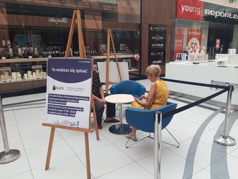 Na zdjęciu mobilny Punkt spisowy NSP 2021. Na zdjeciu przy stoliku w galerii handlowej osoba jest spisywana przez rachmistrza