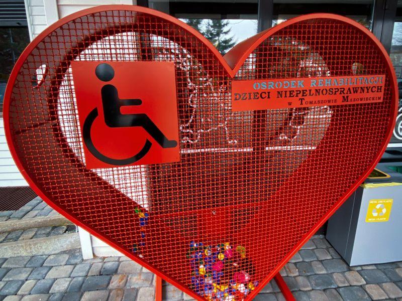 Na zdjęciu pojemnik nas plastykowe nakrętki w kształcie czeronego serca. Pojemnik ustawiony przy wejściu do ORDN