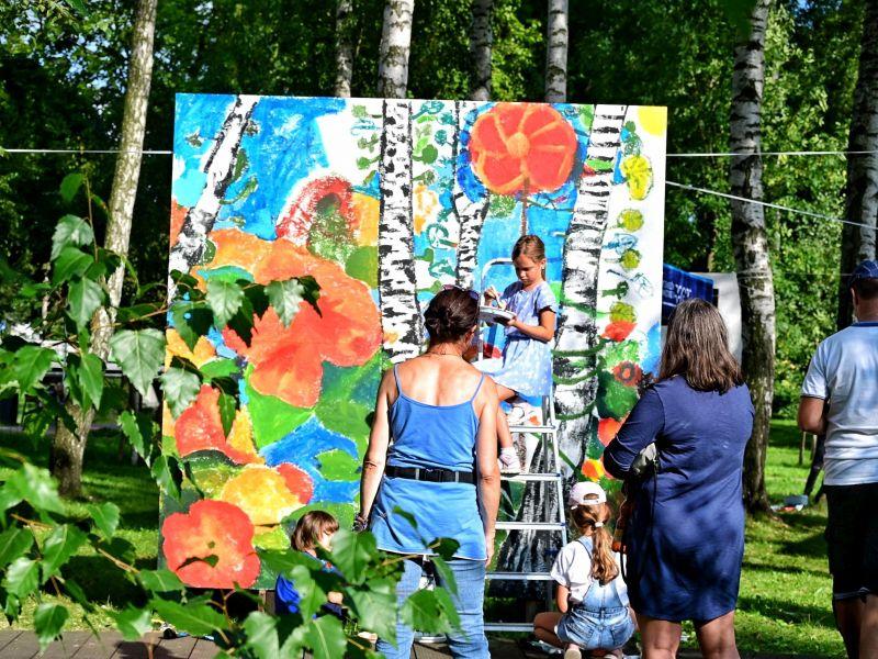 dziecko maluje wielki obraz w parku troje dorosłych się temu przygląda