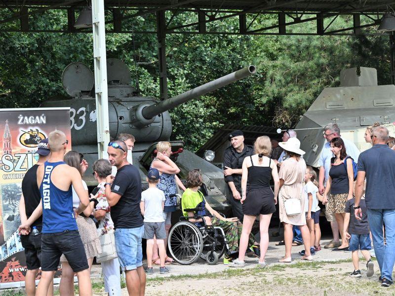 dużo ludzi stoi przy czołgu