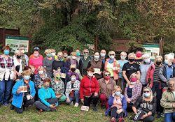 Zdjęcie przedstawia uczestników rajdu z kijkami na terenie Spalskiego parku Krajobrazowego. Uczestnicy stoją w grupie pozując do fotografii, w tle tablice edukacyjne i teren lasu