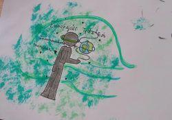 Zdjęcie przedstawia dziecięcy rysunek przedstawiający projekt logo Europejskiego Tygodnia Zrównoważonego Transportu. Na rysunku postać człowieka-drzewa, z której wyrastają zielone gałęzie