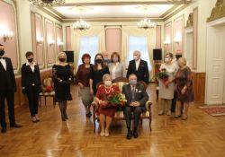 na zdjęciu stoją ludzie w maskach a przed niemi siedzi na kanapie mężczyzna i kobieta z kwiatami