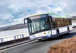 Zdjęcie przedstawia autobus MZK, za szybą przednią widovczny kierowca, autobus przejeżdża przez tamę Zalewu Sulejowskiego