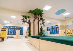 Na zdjęciu wnętrze żłobka, ławki z zielonymi siedziskami, szafki na ubrania, na kolumnie rysunek 3d drzewa